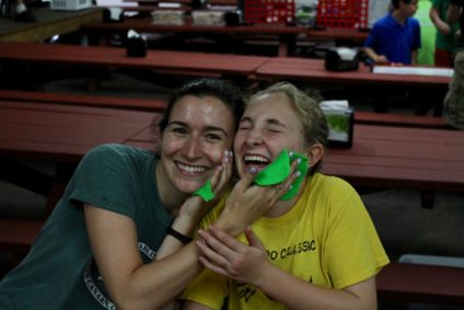 counselor and girl laughing with a green thing on their faces