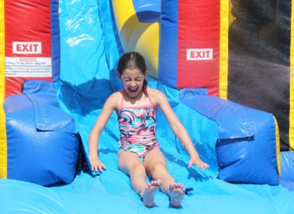 girl coming down inflatable water slide