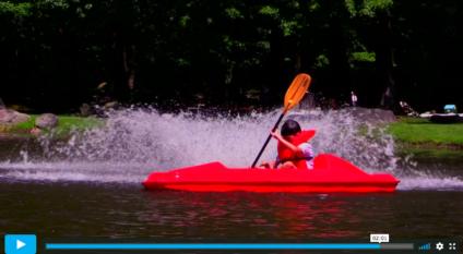 kid paddling boat on a lake